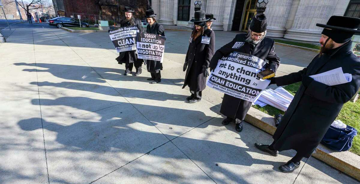 A group of Satmar Orthodox Jews demonstrate their feelings about potential changes to the Education Law in front of the State Education Building Thursday Dec. 20, 2018 in Albany, N.Y. (Skip Dickstein/Times Union)