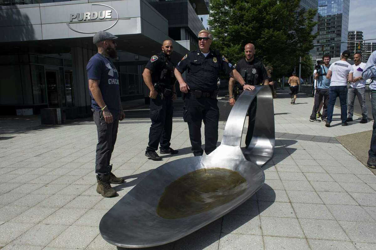 In a file photo from June, Stamford police are shown with a 13-foot-long sculpture of a spoon that was placed outside the headquarters of Purdue Pharma, the makers of the painkiller OxyContin, as part of a protest against the opioid crisis. The sculpture, weighing 700 pounds, depicted the type of spoon addicts use to melt heroin before injecting it.