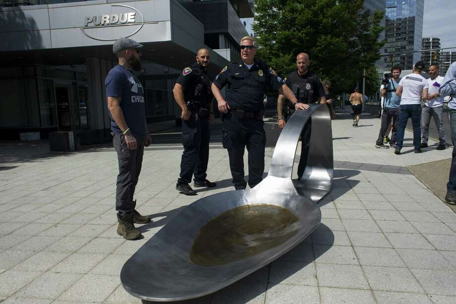 In a file photo from June, Stamford police are shown with a 13-foot-long sculpture of a spoon that was placed outside the headquarters of Purdue Pharma, the makers of the painkiller OxyContin, as part of a protest against the opioid crisis. The sculpture, weighing 700 pounds, depicted the type of spoon addicts use to melt heroin before injecting it. Photo: GREGG VIGLIOTTI / NYT / NYTNS