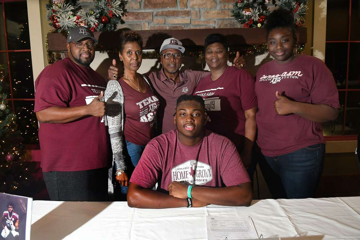 Kenyon Green, front, a senior and an offensive lineman at Atascocita High School, celebrates his signing with Texas A&M with his dad Henry Green, standing from left, his grandmother Debra White, his grandfather James White, his mom Shalonda, and his sister Kamirah at a signing ceremony at the Eagle Springs Clubhouse on Dec. 19, 2018.