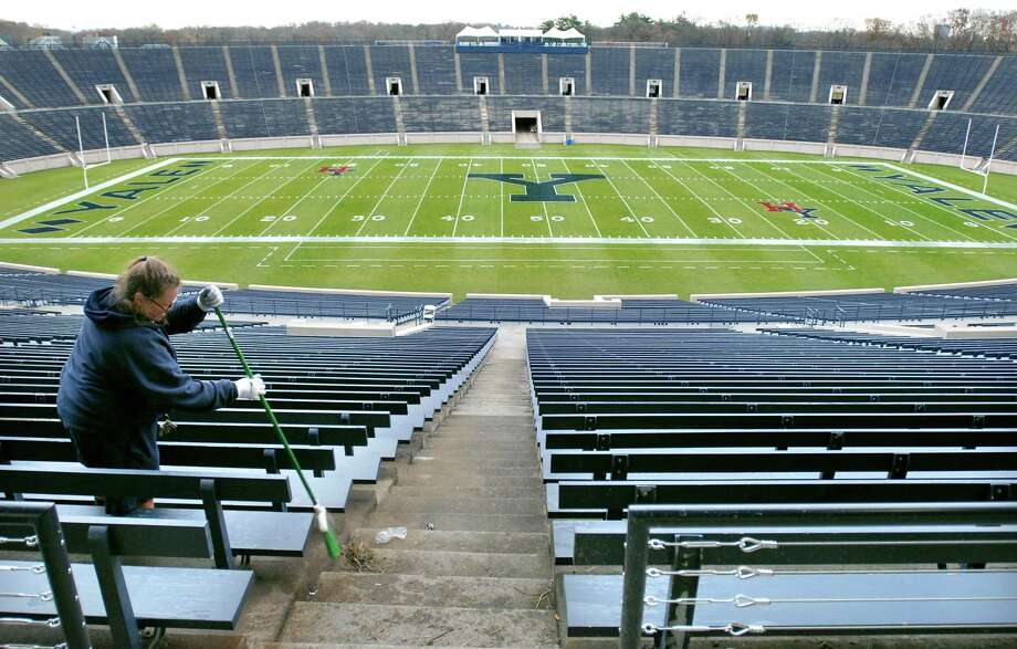 A gardener with Yale University sweeps a seating area at the Yale Bowl in preparation for the Yale/ Harvard game in 2009. Photo: File Photo