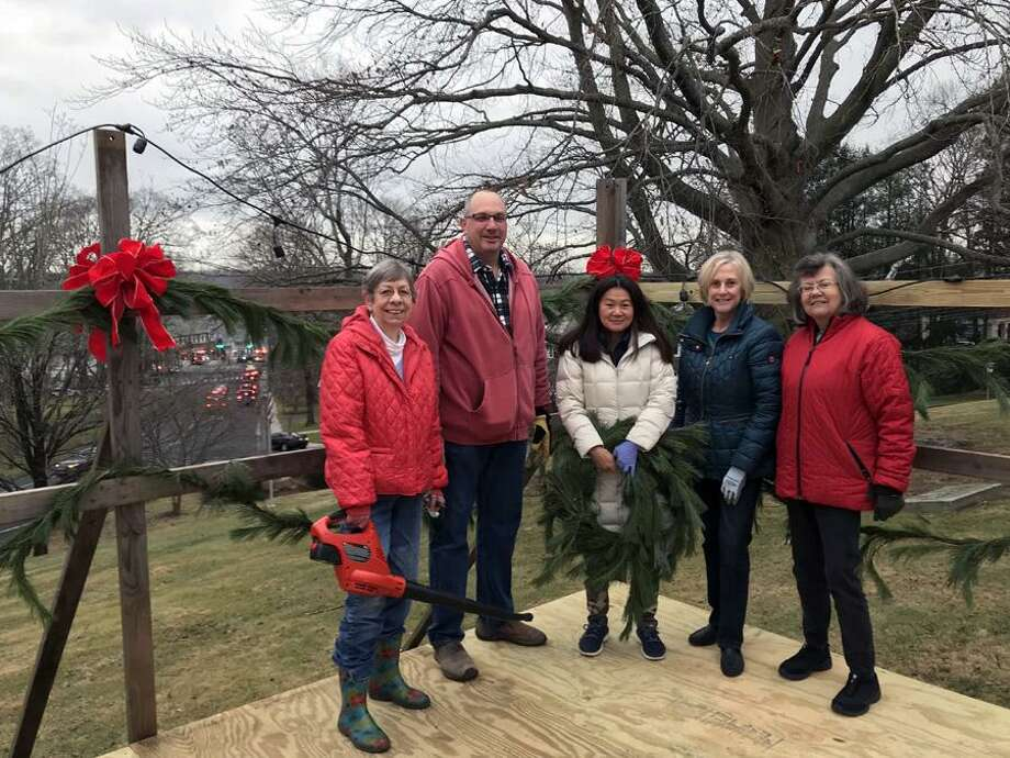 A Carol Sing will be held on God's Acre in New Canaan Christmas Eve. New Canaan Beautification League members, including Kathy Lapolla, Rob Carpenter, Ty Tan, Jill Ernst and Faith Kerchoff, decorated the bandstand on God's Acre for the Christmas Eve Carol Sing. Photo: Contributed