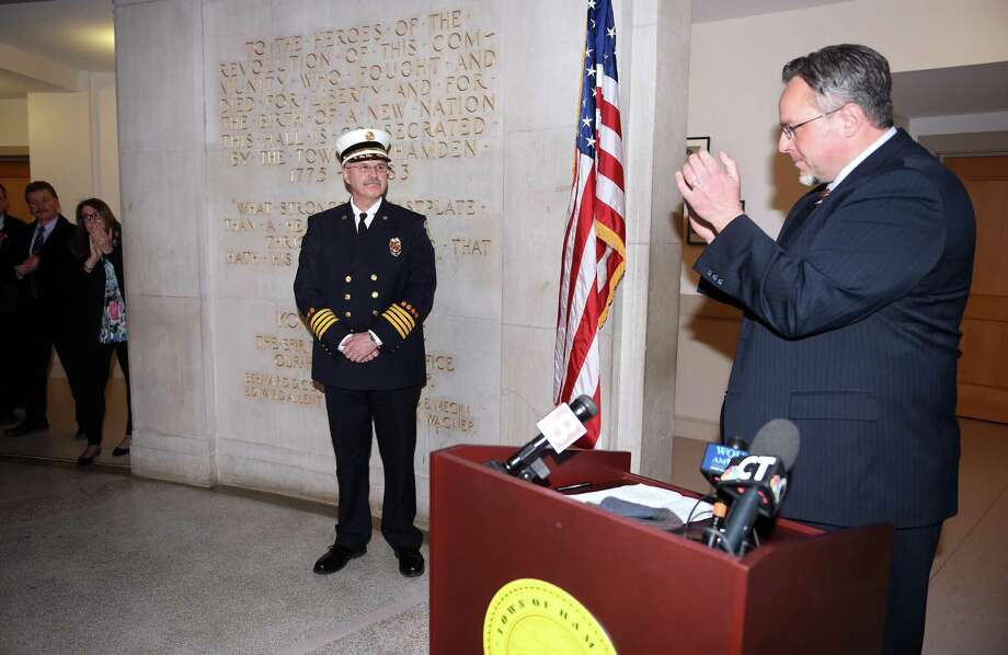 Hamden Mayor Curt Balzano Leng, right,  applauds Deputy Fire Chief Gary Merwede, center,  after announcing his appointment to fire chief at Hamden Memorial Town Hall Thursday. Photo: Arnold Gold / Hearst Connecticut Media / New Haven Register