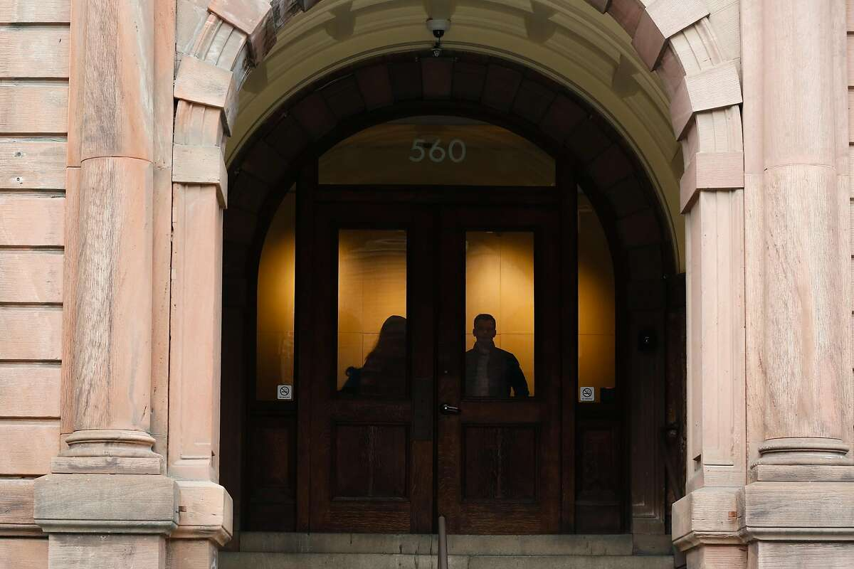 Employees exit and enter the building at Juul headquarters in San Francisco. A bill authored by City Attorney Dennis Herrera and Supervisor Shamann Waltonwould ban companies that sell, manufacture and distribute tobacco products, including e-cigarettes, from city property.