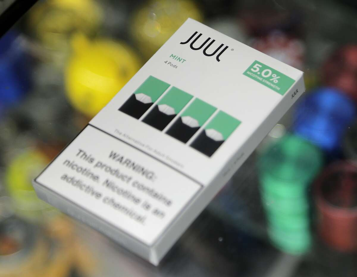 A woman buys refills for her Juul at a smoke shop in New York, Thursday, Dec. 20, 2018.