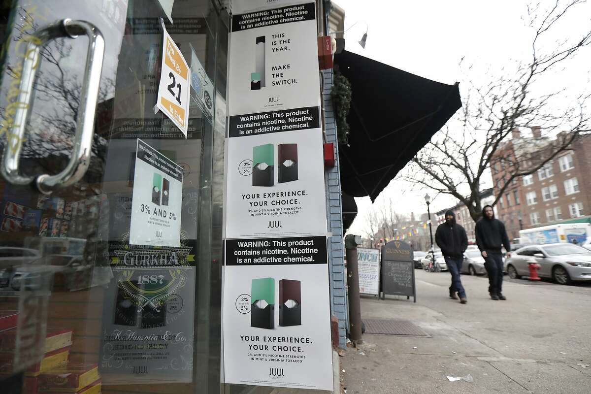 Signs for Juul electronic cigars are seen on the outside of a smoke shop in Hoboken, N.J., Thursday, Dec. 20, 2018. Altria, one of the world's biggest tobacco companies, is spending nearly $13 billion to buy a huge stake in the vape company Juul as cigarette use continues to decline. (AP Photo/Julio Cortez)