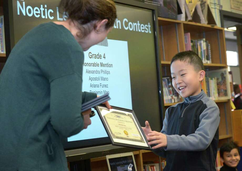 Fourth grader Benjamin Mao accepts his Honorable Mention award from STEM coach Monique Bartling at Jefferson Science Magnet School  on Wednesday. Photo: Erik Trautmann / Hearst Connecticut Media / Norwalk Hour