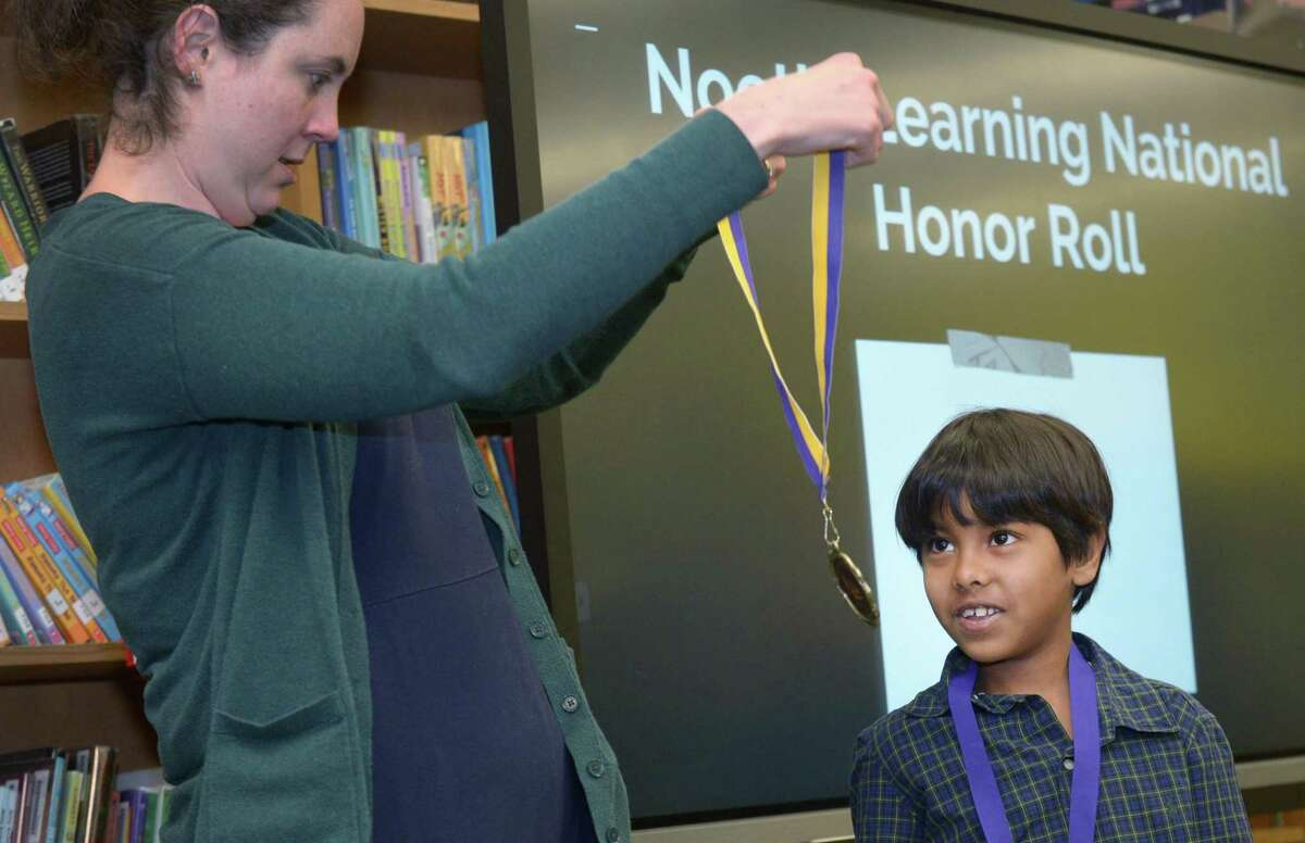 Second grader Div Lal accepst his National Honor Roll medal from STEM coach Monique Bartling as the Jefferson Science Magnet School hosts a breakfast recognizing students who participated or were honored in the Noetic Learning Math Contest Wednesday, December 19, 2018, at the school in Norwalk, Conn. The Noetic Learning Math Contest is a semiannual problem solving contest for elementary and middle school students where the goal is to encourage student interest in math and to develop problem solving skills. During the contest, students are given 45 minutes to solve 20 problems.
