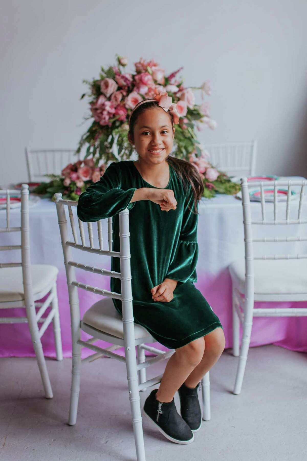 """Aaliyah Leon, 10, wears the """"Joy"""" dress by Houston designer Esther Freedman. Her company is Cuteheads. The flowers are from H-E-B."""