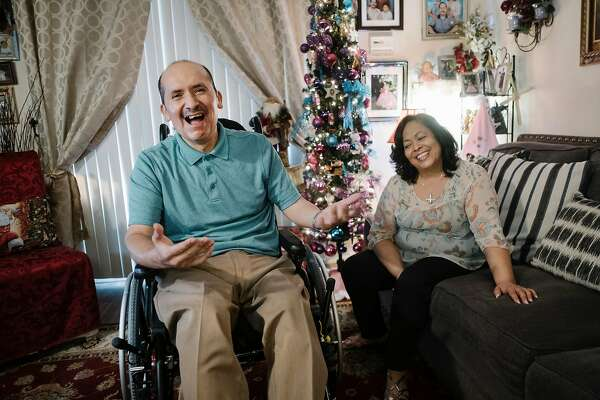 Season of Sharing fund recipients Josefina Calderon and her husband Jose Rios-Estrada share a laugh at their home in Napa, California, on Thursday, December 6, 2018. The San Francisco Chronicle's Season of Sharing fund help buy a lift machine for Jose Rios-Estrada, who suffers from multiple sclerosis, to help him get in and out of bed.