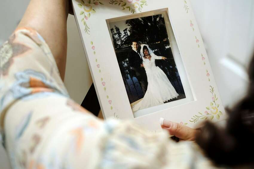 Calderon adjusts a wedding picture of her and her husband, Rios, whom she met in an English-language class.