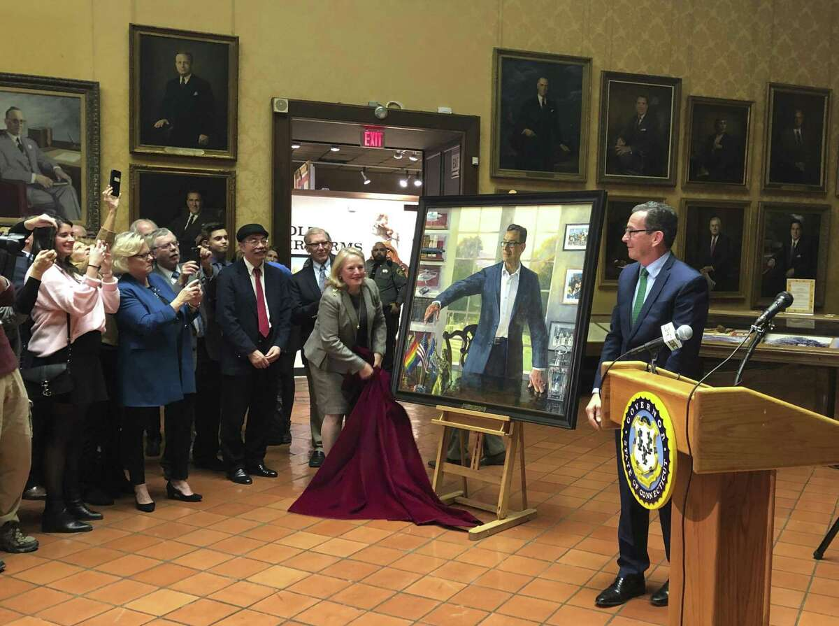Outgoing Gov. Dannel P. Malloy, right, and his wife Cathy, center, unveil the Democrat's official state portray during a ceremony at the Museum of Connecticut History in Hartford, Conn., Thursday, Dec. 20, 2018. The Democrat leaves office on Jan. 9. (AP Photo/Susan Haigh)