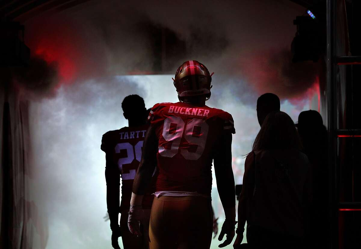 DeForest Buckner (99) and Jaquiski Tartt (29) enter the field before the San Francisco 49ers game against the Dallas Cowboys at Levi's Stadium in Santa Clara, Calif., on Thursday, August 9, 2018.