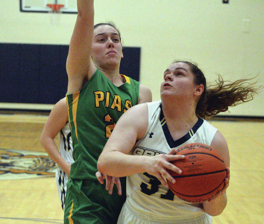 Father McGivney senior Caitlyn Pendall, right, drives to the basket during Thursday's game against Piasa Southwestern at FMCHS. Photo: Scott Marion/Intelligencer