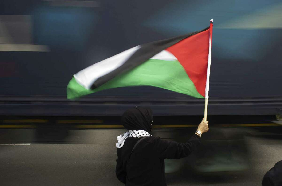TOPSHOTS A woman holds a Palestinian flag as a truck passes by, during a protest against Grammy-winning American musician Pharrell Williams near the Grand west Casino where he was holding a concert in Cape Town, on 21 September, 2015. Supporters of the Boycott, Divestment and Sanctions (BDS) campaign were protesting against the singer's partnership with major South African retail group Woolworths, over its imports from Israel. BDS accuses Woolworths of importing Israeli agricultural produce grown in the occupied Palestinian territories, a charge the company denies. AFP PHOTO / RODGER BOSCHRODGER BOSCH/AFP/Getty Images