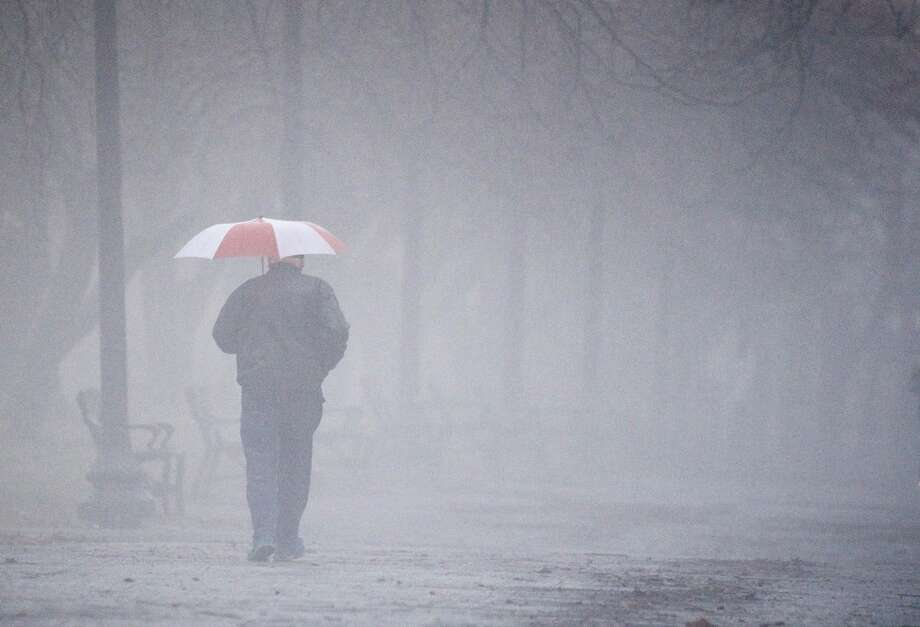 The day will get off to a foggy start on Tuesday. In this photograph, early morning fog shrouds a man as he walks through Albany's Washington Park on Friday, Dec. 21, 2018. Forecasters say rain should continue through the day, causing the potential for flooding. Photo: Skip Dickstein / Times Union