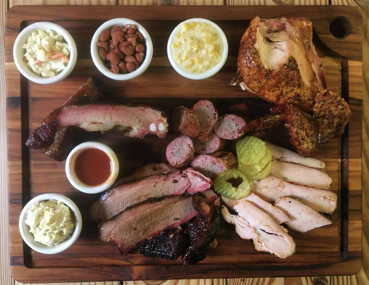 The Heavy's Bar-B-Que board with (from top left) cole slaw, beans, creamed corn, chicken, turkey, sausage, brisket, potato salad and pork ribs.