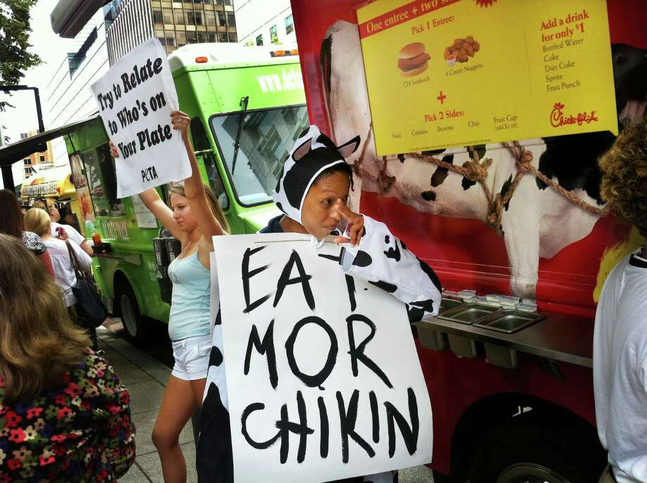 """Tessa Callan, left, is part of a People for the Ethical Treatment of Animals protest against the Chick-fil-A restaurant's food truck in Washington, D.C. on July 13, 2012. Meanwhile Kyra Coffie came dressed in a cow costume, which earned her a free lunch. For July 13, """"Cow Appreciation Day"""" Chick-fil-A restaurants awarded free meals to any customer fully dressed as a cow. Photo: Washington Post Photo By Michel Du Cille / The Washington Post"""
