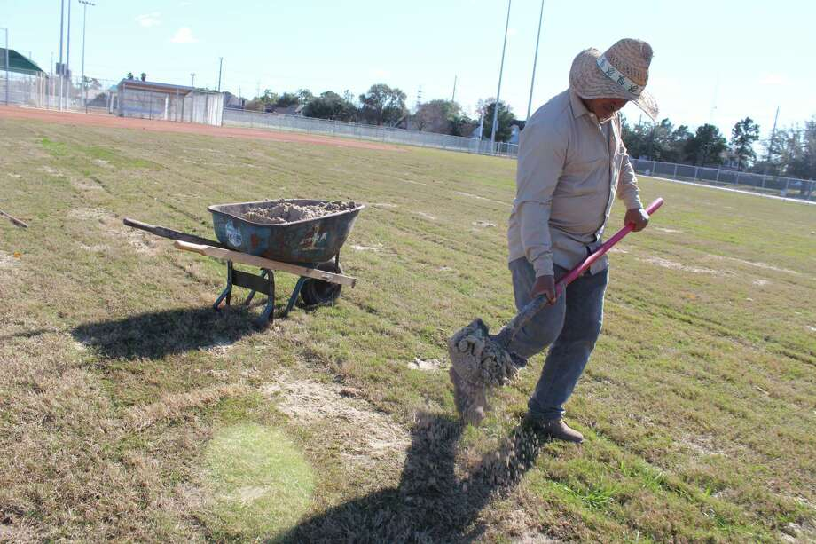 Apolinar Ortiz fills in holes left by rain on one of the softball fields at the Youth Sports Complex in Deer Park. Weather has been a factor in delaying completion of the renovation projects.