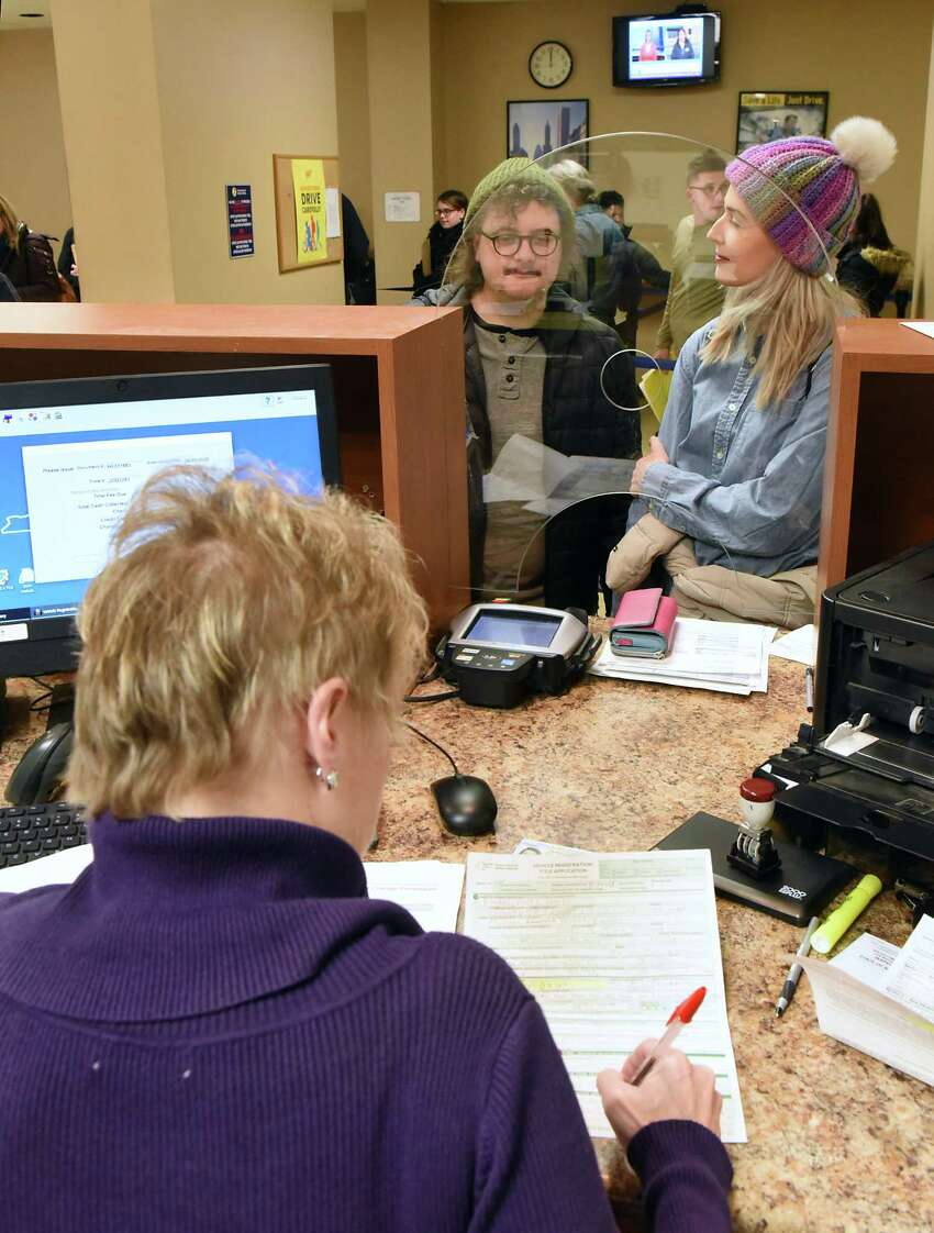 Michael and Kendall Hoeft switch their Florida registrations to New York State registrations at the Department of Motor Vehicles on Thursday, Dec. 20, 2018 in Troy, N.Y. The state Association of County Clerks will push this coming year for the state reimbursement on DMV services to be upped from 12.7 percent to 25 percent. (Lori Van Buren/Times Union)