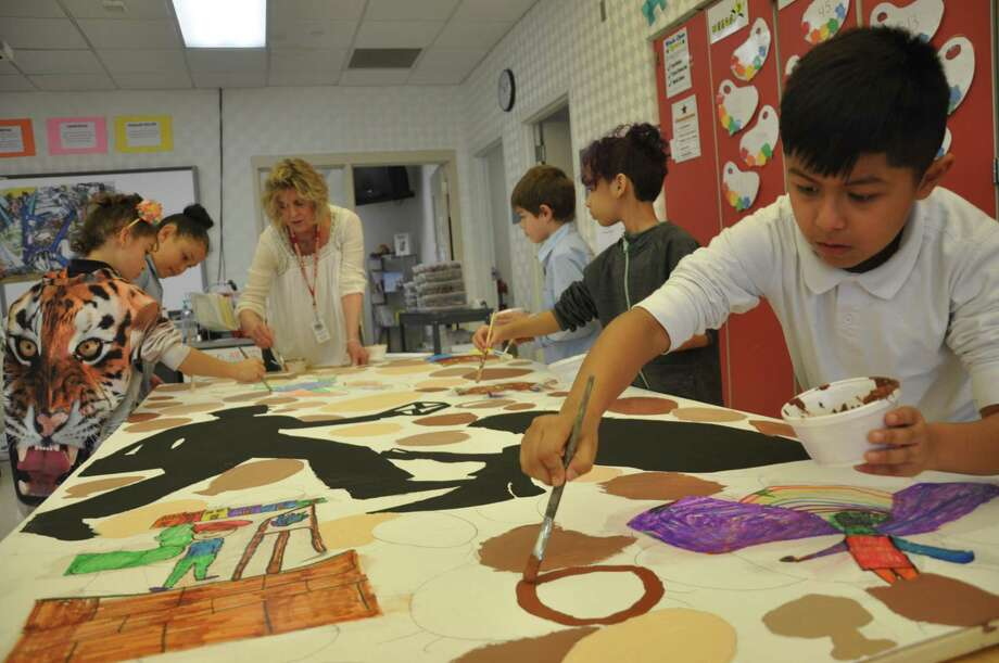 AMP teaching artist Kathy Reddy with works with Rotella students painting a mural panel. Photo: American Mural Project / Contributed Photo