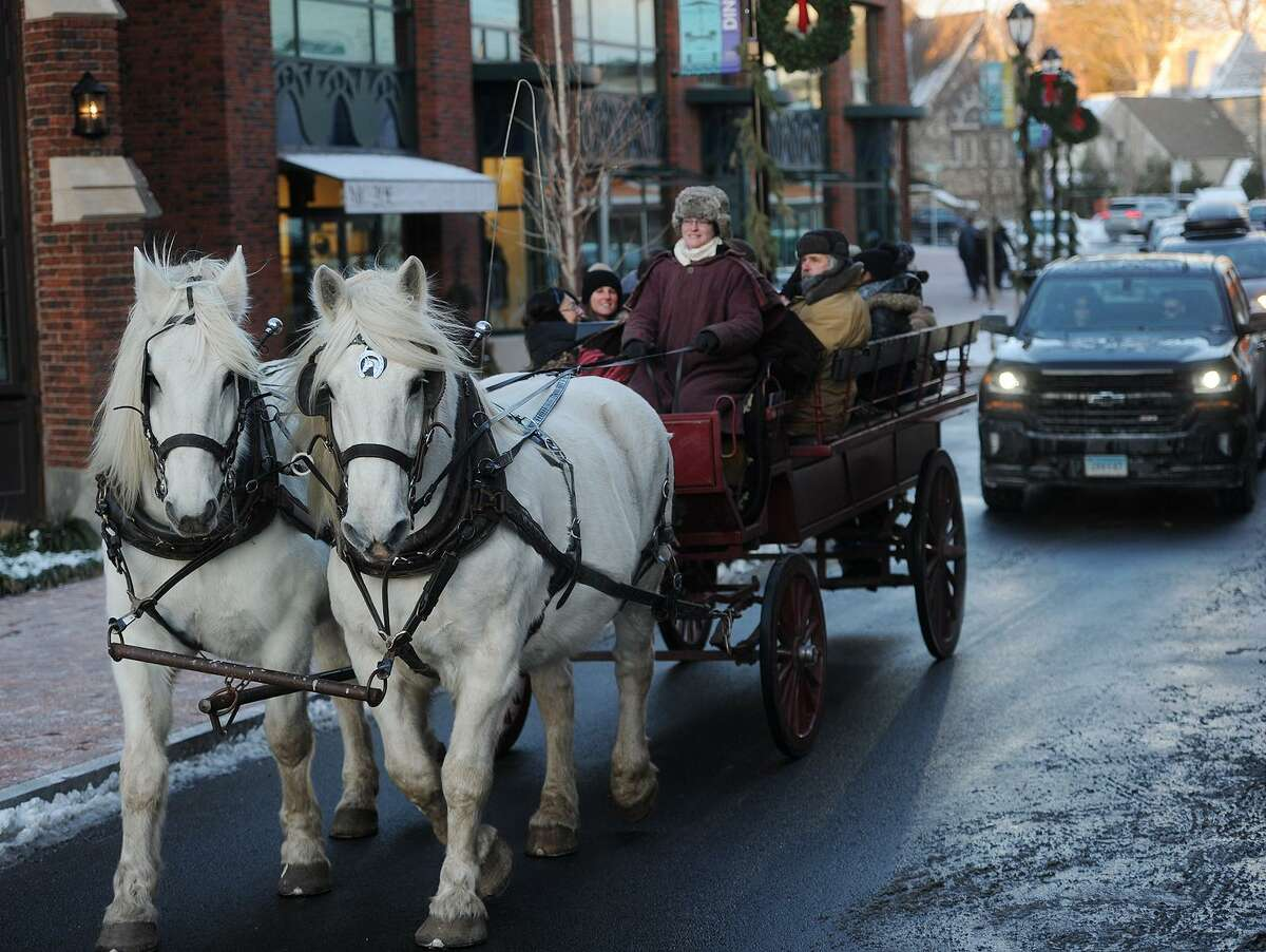 Rachel Sherman, from Allegra Farms in East Haddam, and her team of Percheron draft horses give carriage rides as part of First Night 2018 festivities in Westport, on New Year's Eve last year.