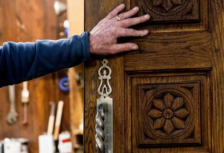 Tom Kieninger, owner of the Barn Woodshop, runs his hand over a refinished door inside the shop that has been in his family for decades. It is part of the Menlo Park complex known as the Allied Arts Guild. Photo: Jessica Christian / The Chronicle