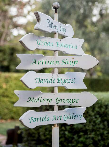 Wooden arrows point guests to the variety of shops and businesses inside the Allied Arts Guild complex in Menlo Park. Photo: Jessica Christian / The Chronicle