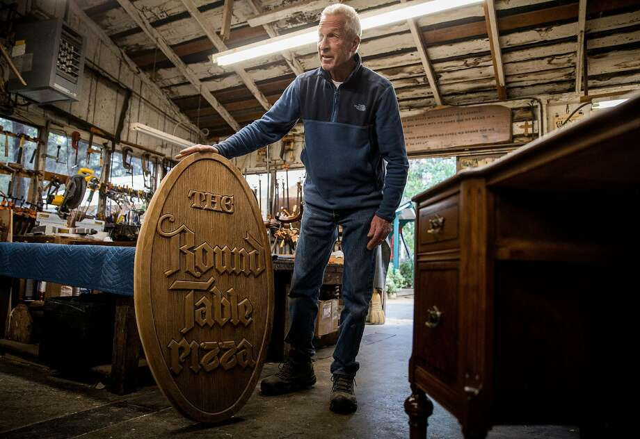Tom Kieninger, owner of the Barn Woodshop, in Menlo Park, shows off the original 1955 wooden Round Table Pizza sign, which was brought into the shop for refinishing at the behest of the founder's son. Photo: Jessica Christian / The Chronicle