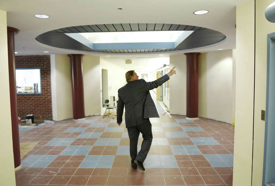 Principal Gene Schmidt shows the newly-repaired main entrance lobby at Cos Cob School in the Cos Cob section of Greenwich, Conn. Wednesday, Dec. 19, 2018. Displaced Cos Cob School kindergartners, first- and second-graders will return on Jan. 2, concluding nearly three months in makeshift classrooms at Parkway and Old Greenwich Schools after major flooding caused damage forcing students to be relocated. Photo: Tyler Sizemore / Hearst Connecticut Media / Greenwich Time