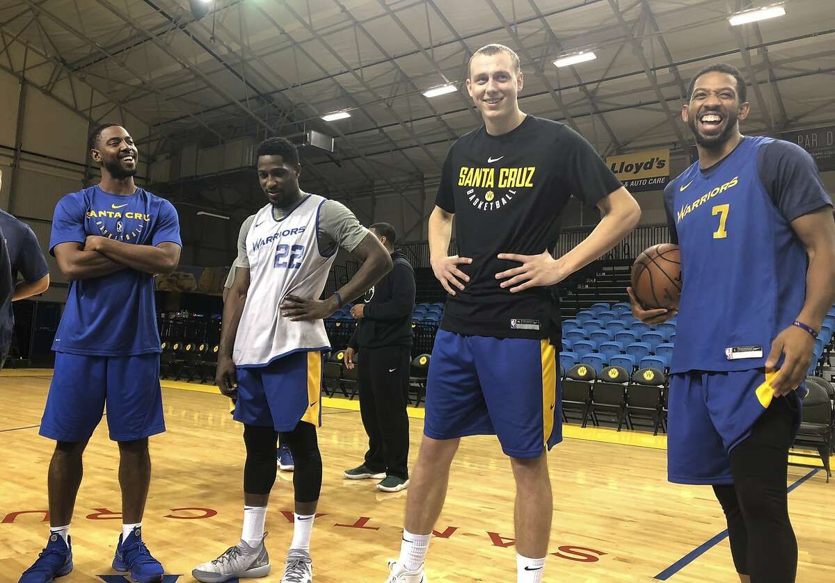 In this Dec. 4, 2018 photo, from left, Santa Cruz Warriors coach Aaron Miles, guard Will Cherry, Alen Smailagic and Darius Morris talk after their basketball practice in Santa Cruz, Calif. As the Santa Cruz Warriors huddled together after practice, Darius Morris gave a quick recap of his adventure to the Arizona desert a day earlier to interview with the Suns. Phoenix needed a point guard with Devin Booker's hamstring injury, and Morris was in the mix. Coach Aaron Miles, who so wishes he were still playing, had to stand in leading the offense given Morris' absence. Such is life in the topsy-turvy, changing-by-the-day G League, when Golden State or another club might come calling at a moment's notice to swipe a top player for promotion to the NBA. (AP Photo/Janie McCauley)