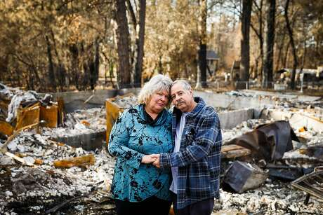 (l-r) Susan Matoes and her husband Frank Matoes stand in front of their property which was destroyed in the Camp Fire in Paradise, California, on Wednesday, Dec. 19, 2018. The Matoes' previous home was destroyed in the Tubbs Fire last year in Santa Rosa.