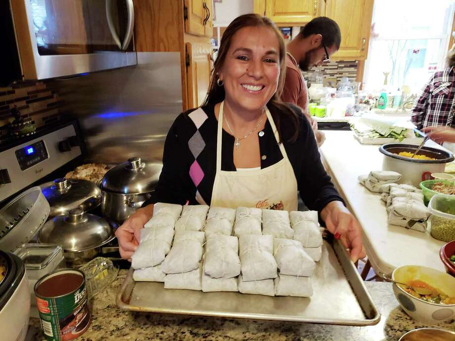 Nellie Arias holds a tray of finished homemade Christmas tamales. Photo: Frank Whitman / For Hearst Connecticut Media / Norwalk Hour freelance