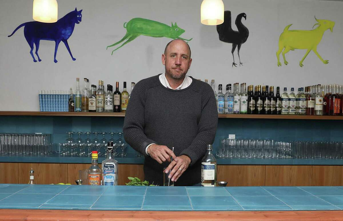 Bar owner Thad Vogler makes a Mojito at Obispo, a rum bar in the Mission. Behind him is art seen from Bill Traylor on the walls.