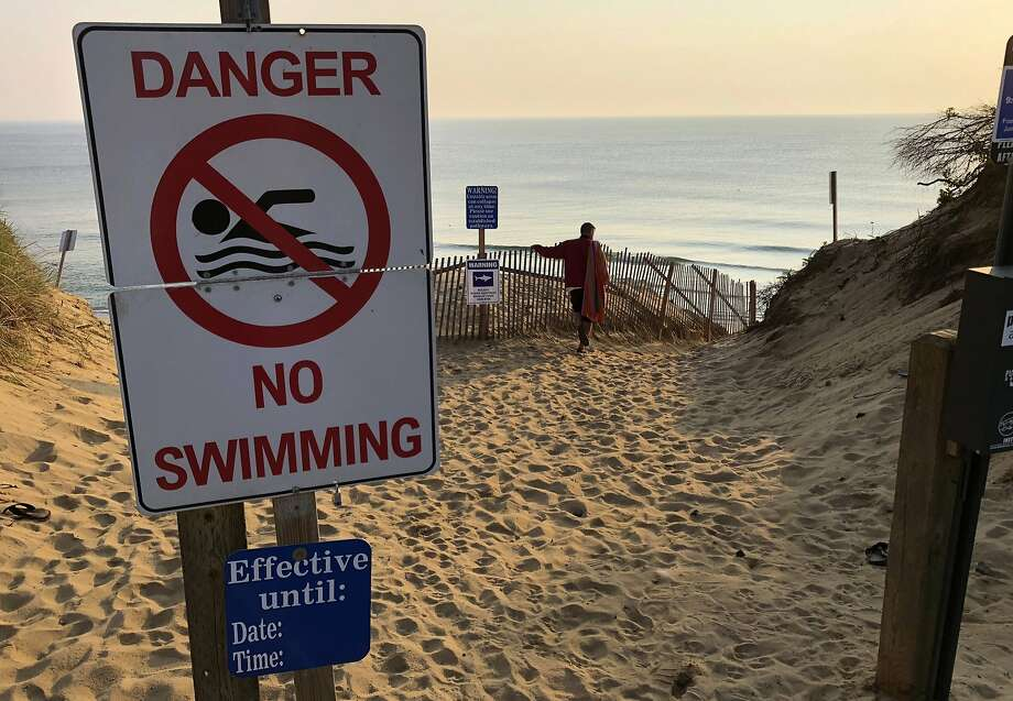 A sign prohibits swimming at the beach in Truro in August after a man was attacked there by a shark. Photo: William J. Kole / Associated Press