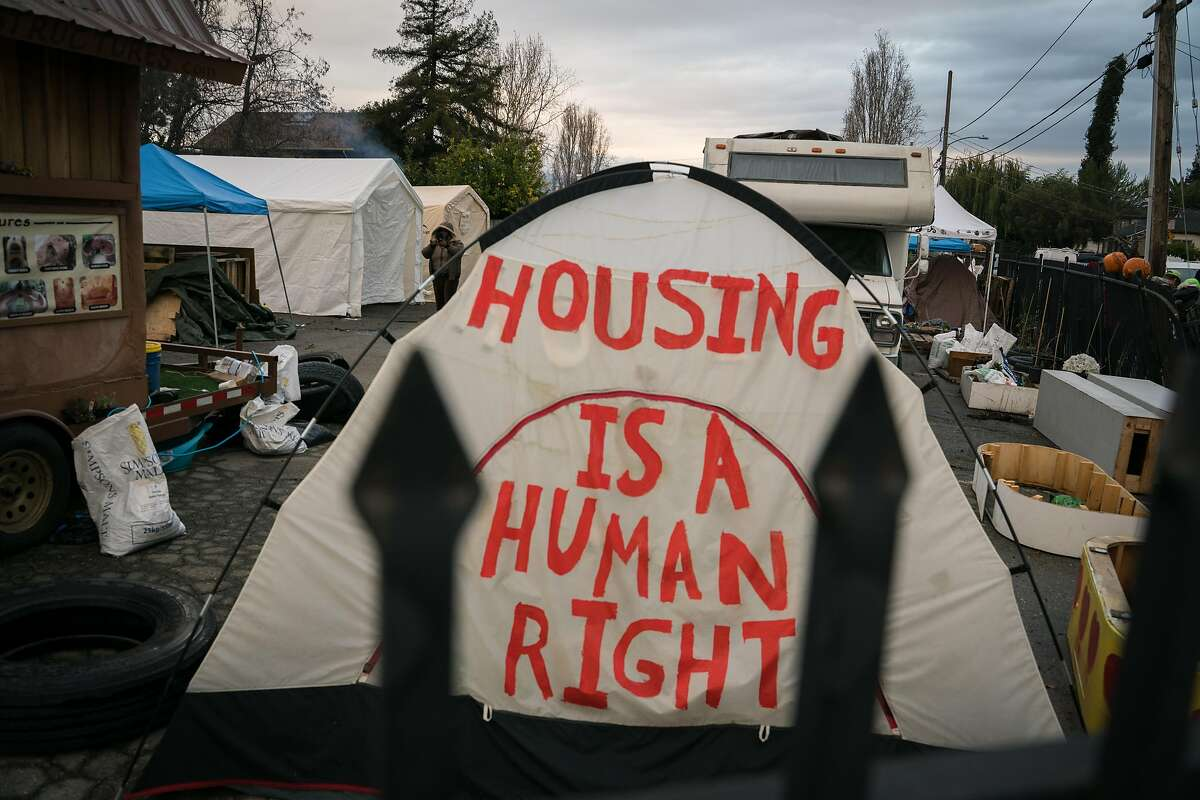 A message is painted on a tent standing in the Dignity Village homeless encampment in Oakland, Calif. on Wednesday, Dec. 5, 2018.