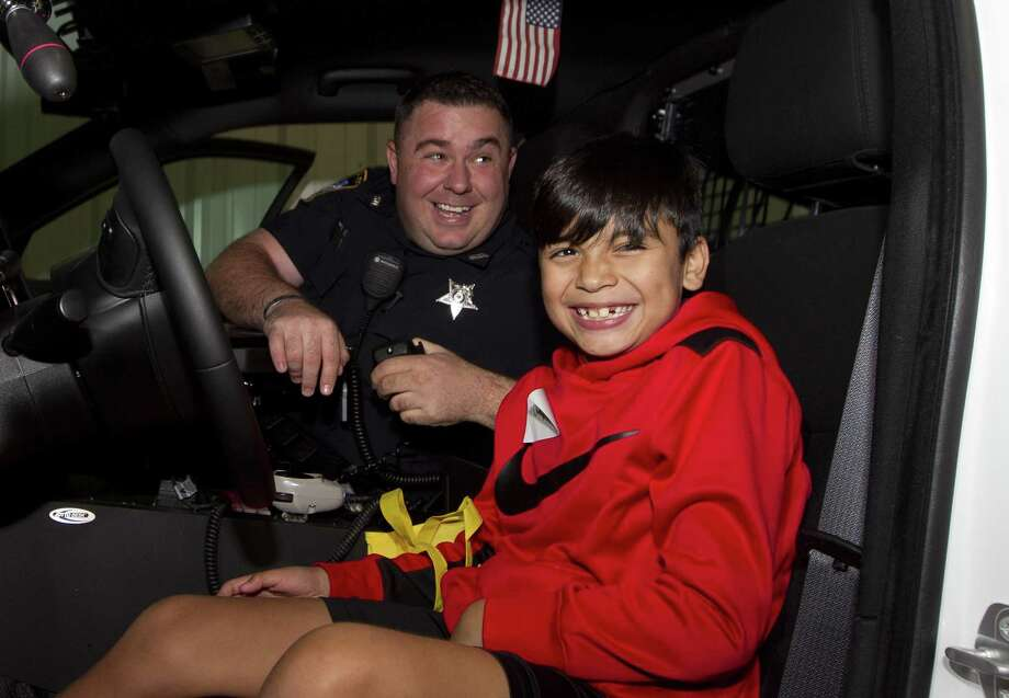 Jorge Alacala shares a laugh next to Zach Vercher, with the Montgomery County Sheriff's Office, after playing with the police car's lights during the department's annual toy drive Friday, Dec. 21, 2018, in Conroe. Operation Blue Elft provided gifts to 1,200 area children. Photo: Jason Fochtman, Houston Chronicle / Staff Photographer / © 2018 Houston Chronicle