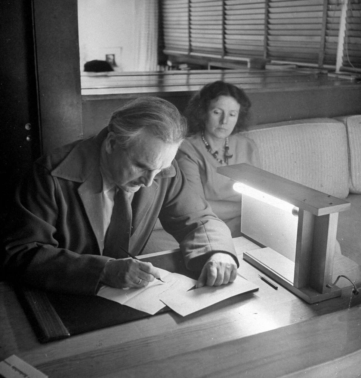 Architect Richard Neutra sitting with wife at home, working on lighting. (Photo by Ralph Crane/The LIFE Images Collection/Getty Images)