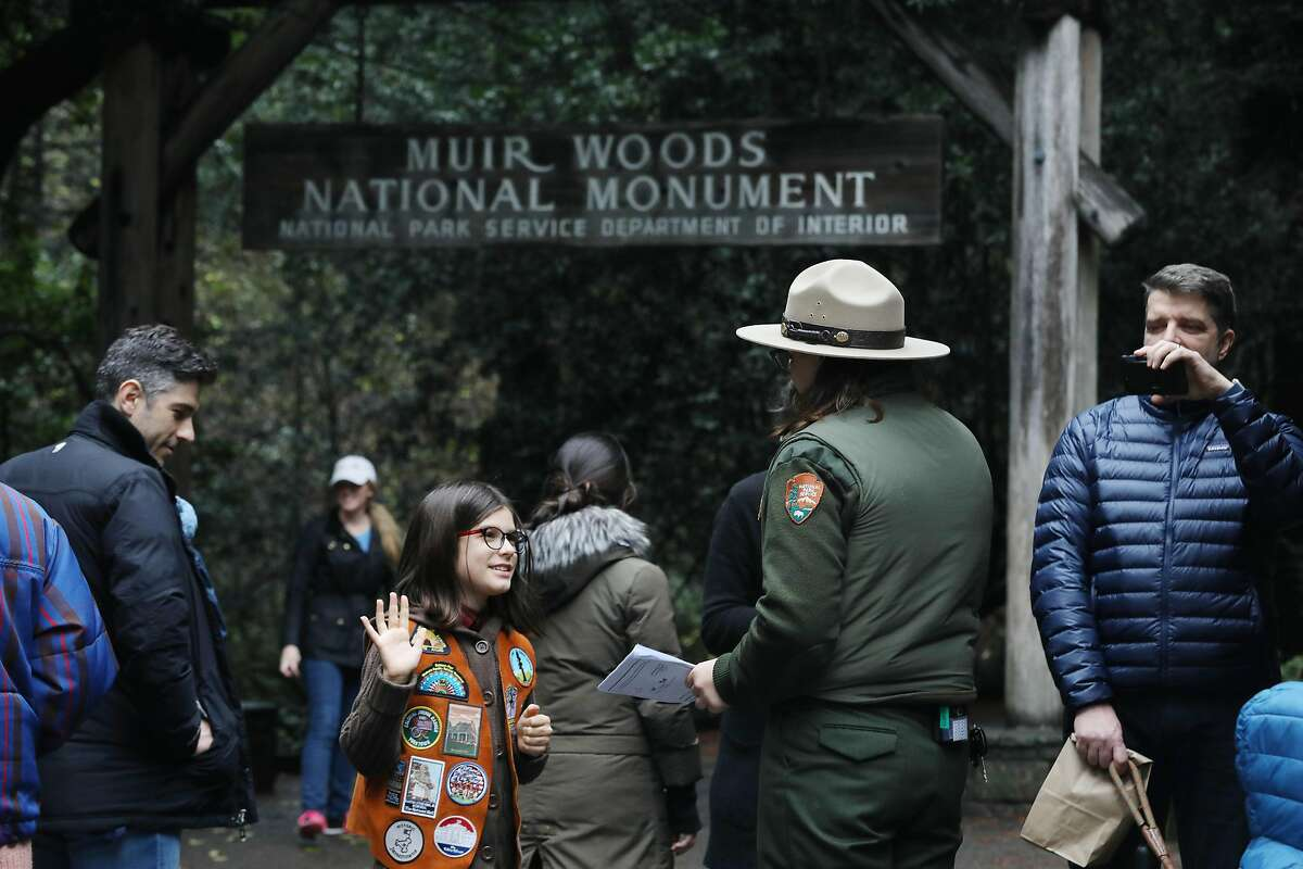 Adele Nico (l to r), 9, of Los Angeles takes a Junior Rangers oath with Ranger Ellen Spicer as her father David Nico documents on Wednesday, December 19, 2018 in Muir Woods National Monument in Mill Valley, Calif.