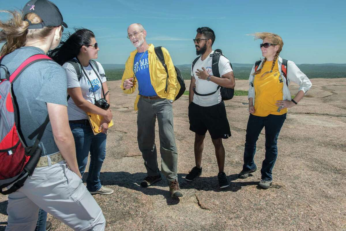 David Turner, Associate Professor of Environmental Science at St. Mary's University, center, leads geology students on a hands-on learning experience to Enchanted Rock State Natural Area.