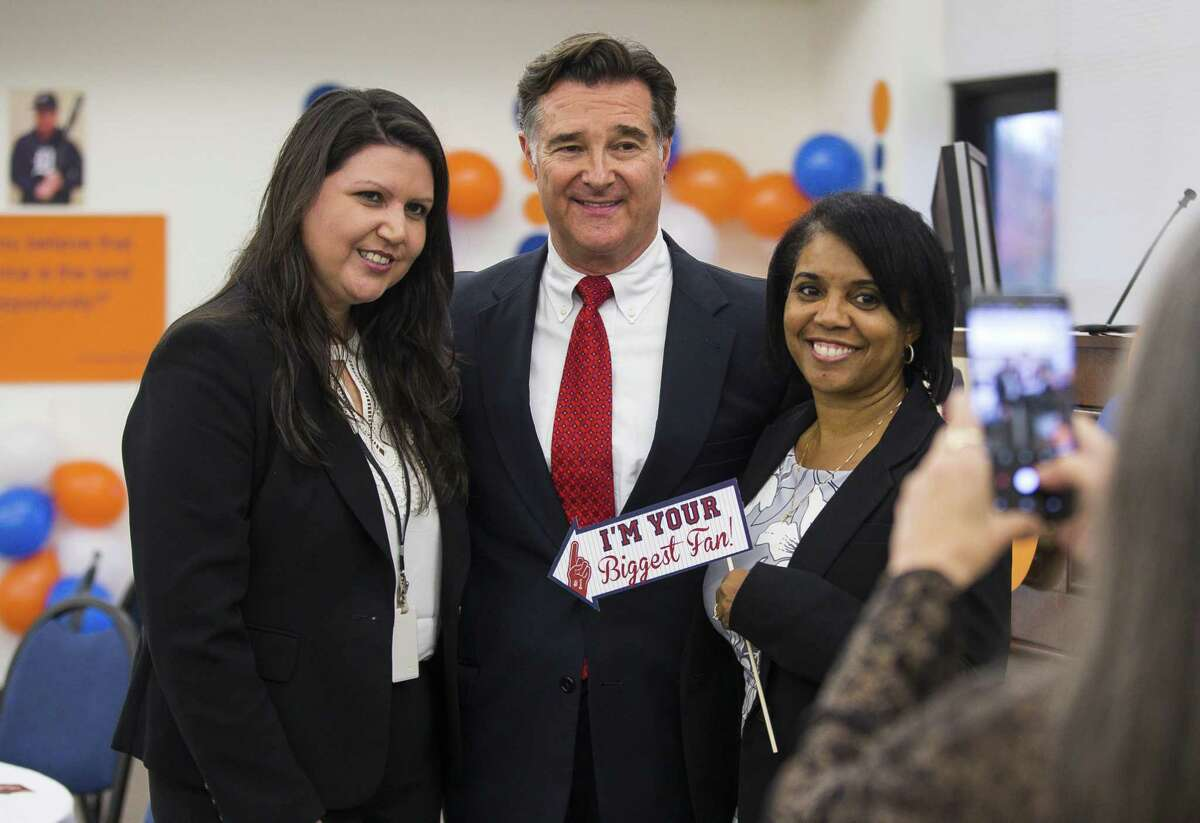 Fort Bend County District Attorney John Healey is shown with Sandra Salas (left) and Tyra McCollum (right), both with the juvenile division of the District Attorney's Office, during Healey's retirement party at the Gus George Academy in Richmond, Thursday, Nov. 29, 2018 in Houston. Healey has served for 26 years in the role.