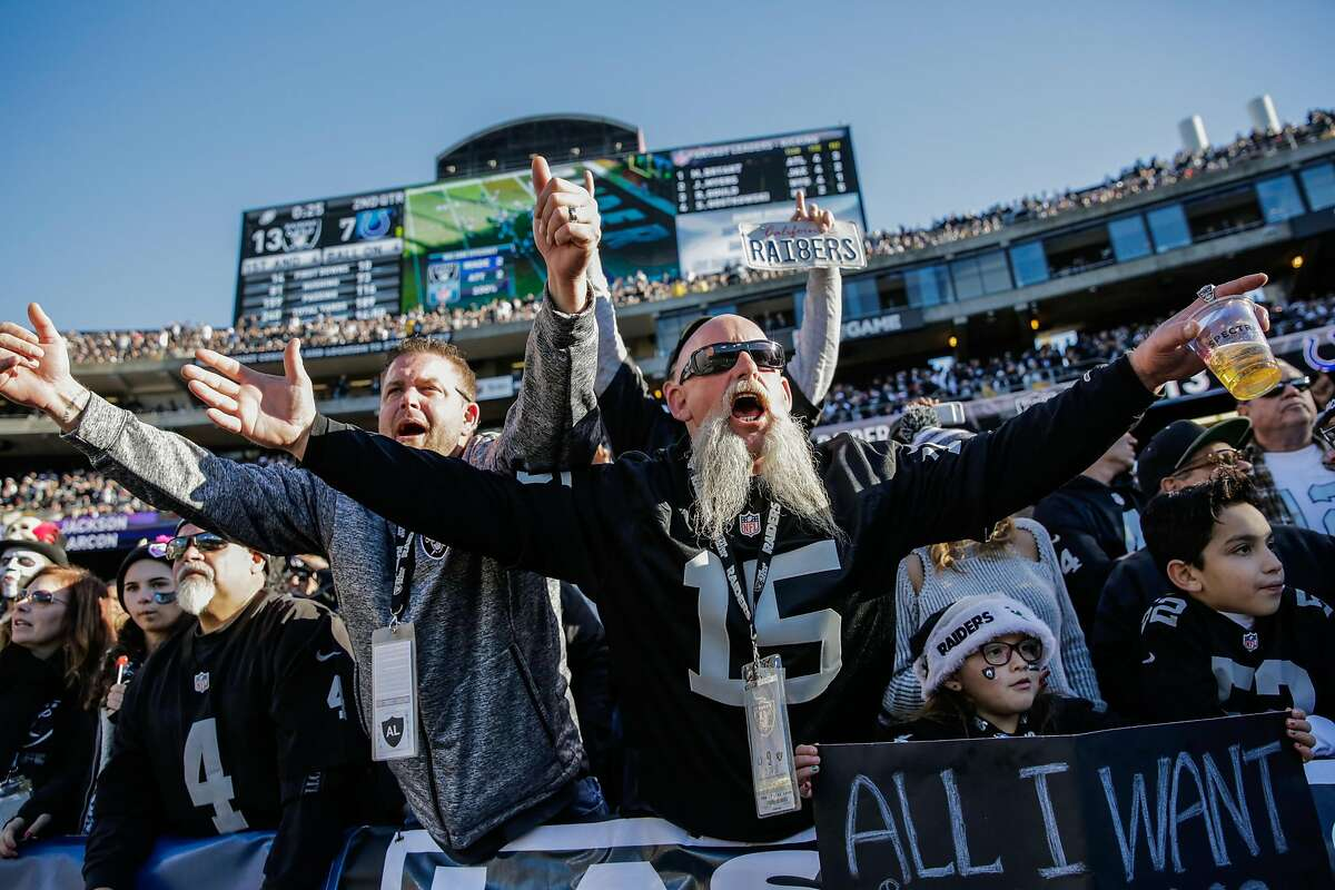 Raiders fans Denny Day and Joe Nunes (right) cheer during a game between the Oakland Raiders and the Indiana Colts, in Oakland, Calif., on Saturday, Dec. 24, 2016.