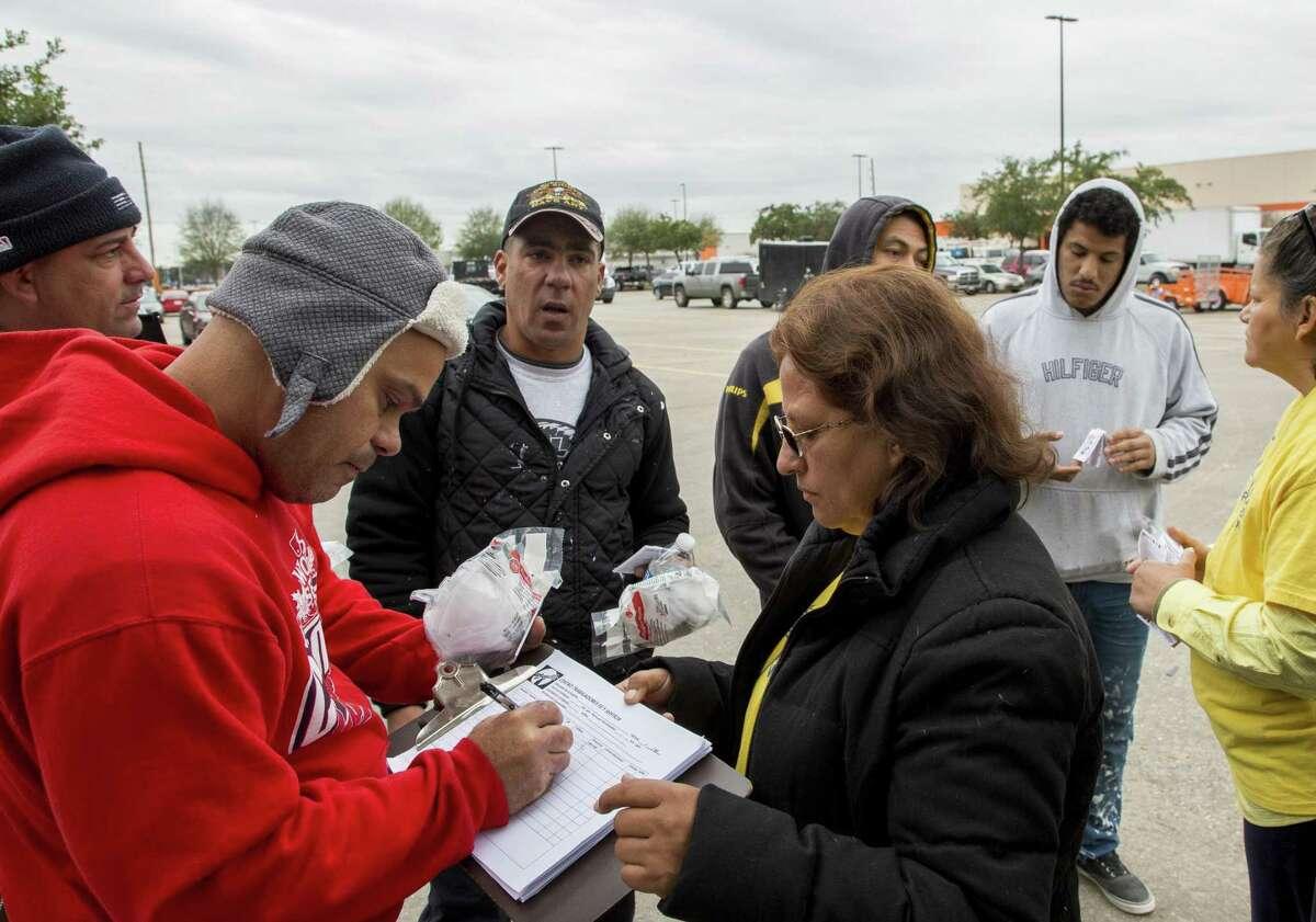 Sylvia Rangel (centro) toma información de contacto de los jornaleros que estaban buscando trabajo en el estacionamiento de una de las tiendas Home Depot de Houston el miércoles 12 de diciembre de 2018.