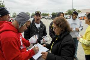 Silvia Rangel, center, collects contact information from day laborers at a Home Depot parking lot Wednesday, Dec. 12, 2018, in Houston.