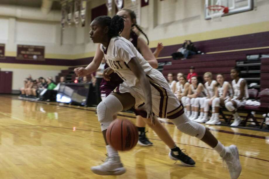 Magnolia West sophomore Kamari Portalis (4) drives past Magnolia junior Audrey Andrews (23) during a District 19-5A girls high school basketball game Friday, Dec. 21, 2018 at Magnolia West High School in Magnolia. Photo: Cody Bahn, Houston Chronicle / Staff Photographer / © 2018 Houston Chronicle