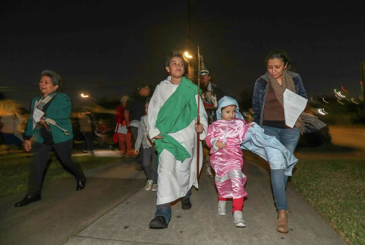 Alexander Martinez, 7, and his sister Angela, 4, portrayed Joseph and Mary are helped by their mother Elsy as they battled gusty winds during the Posadas at the Blessed Sacrament Catholic Church Thursday, Dec. 20, 2018, in Houston. The re-enacting tradition of posadas, is to honor the journey of Mary and Joseph had as they arrived in Bethlehem to deliver the baby Jesus. The event was hosted by Religious Sisters of the Comunidad Apostólica de María Siempre Virgen.