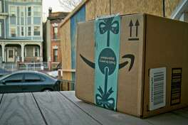 This image taken from video shows an Amazon package containing a GPS tracker on the porch of a Jersey City, N.J. residence after its delivery. The explosion in online shopping has led to porch pirates swiping packages from unsuspecting residents. Texas has increased the penalty for mail theft in an effort to curb the problem.