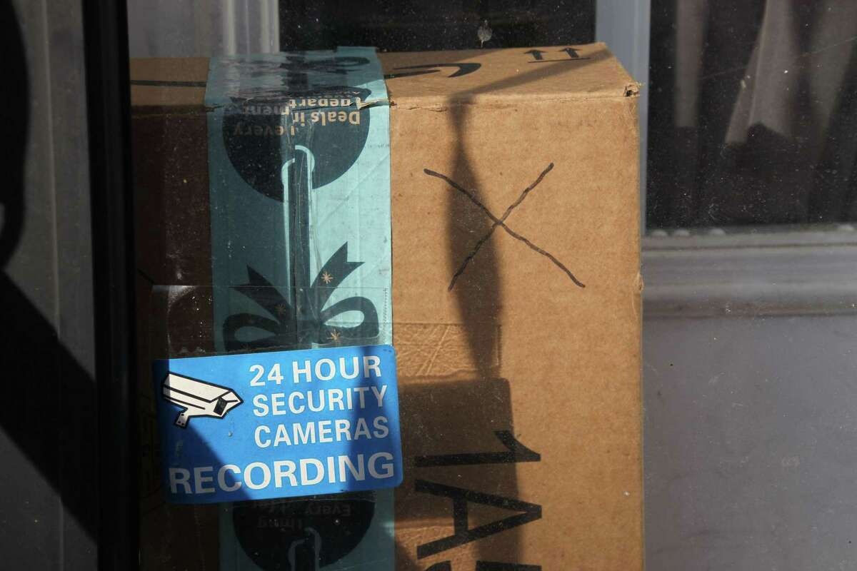 """Baltimore resident Rosemarie Dumhart uses a decoy package, marked with an X, to discourage the so-called """"porch pirates"""" operating in the Canton area of Baltimore, Maryland, on December 17, 2018. - The thieves are filmed by a camera located above the door. (Photo by Sébastien DUVAL / AFP)SEBASTIEN DUVAL/AFP/Getty Images"""
