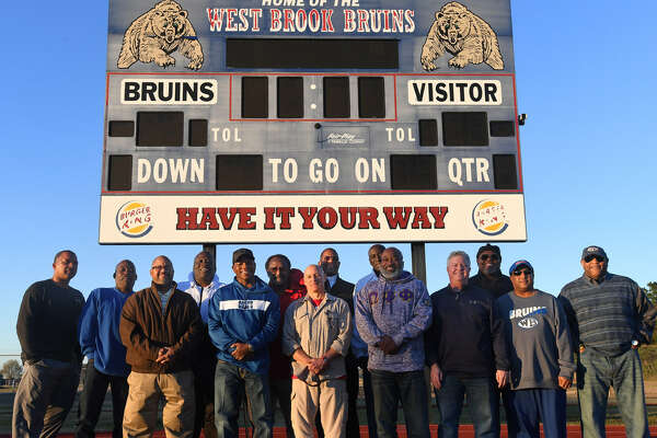 Fourteen members of the 1982 West Brook football team pose for a photo on the track at Alex Durley Stadium on Thursday. The inaugural season for the Bruins, the team was the first to play in a state tourney and the last since the 2018 team who plays for the title today. Photo taken Thursday, 12/20/18