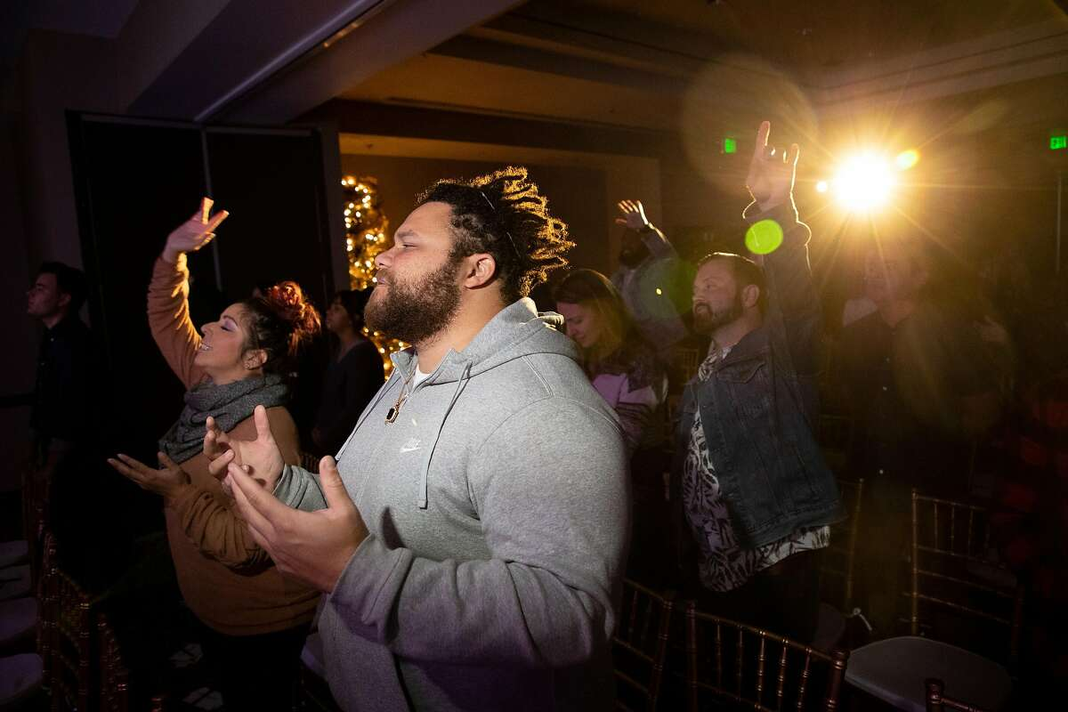 Jordan Lee, of Campbell, prays during CenterSet church services at Hotel Valencia Santana Row on Sunday, Dec. 9, 2018, in San Jose, Calif. Ali Roohi left behind a career in engineering to become a pastor in Silicon Valley.